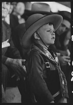young cowboy watching the rodeo: san angelo fat stock show - 1940.  san angelo, texas