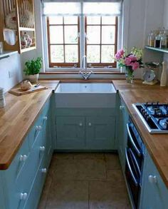 ooh, really love the charm of this tiny u shaped kitchen with its painted blue cabinets, wood counters and farmhouse sink... plus the plate rack...