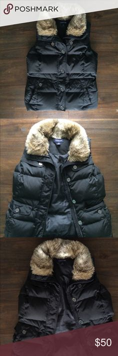 Lands End Puffer Vest Outerwear Winter A chic black puffer vest by Lands End that looks good with everything and creates a flattering figure. Has four front pockets, a button-and-zipper front enclosure, and faux fur trim around the neck. Also comes with two extra buttons which are attached inside of the vest next to the care tag. This has always been one of my favorite wardrobe staples and I hope it will be the same for you. Mint condition. Size small 6-8. Lands' End Jackets & Coats Vests