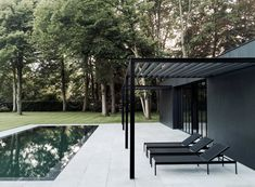 Patio in front of black house with swimming pool