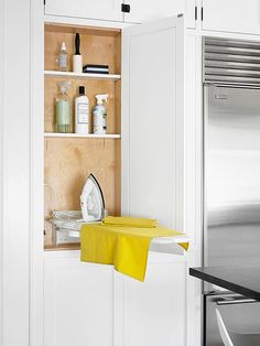 In a kitchen that takes advantage of every square inch of space, an ironing station is another smart addition. A compact flip-down ironing board fits neatly into a shallow cabinet. Two extra shelves organize ironing supplies.