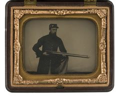 """Ninth Plate Ambrotype of Cpl. Abner Colby, Co. G., USSS   A horizontal view of Colby uniformed in ubiquitous green frock coat kneeling with an early civilian target rifle with telescopic sight adopted for use by Berdan's famous Sharpshooters. Scratched on the silver backing plate is, """"A.D. Colby/Co G./N.H./U.S.S.S."""""""