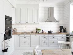 biała kuchnia skandynawska ze srebrnymi uchwytami w kształcie muszli,drewnianymi blatami i stalowym okapem i płytką glazurowaną białą cegiełką na ścianie - Lovingit.pl
