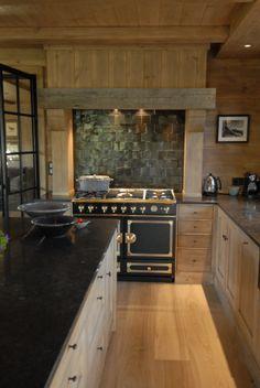 Rustic kitchen in Norway with black Cornue stove & black tile backsplash - Anette Wessel