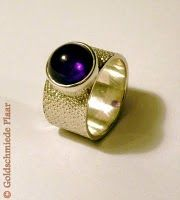 Solid ring with purple cabachon