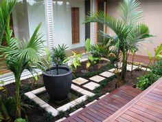 petite terrasse en bois composite avec des palmiers et fontaine décorative