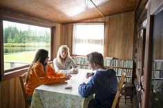 Three Teenagers Playing a Game of Cards in a Cabin - Cavan Images/Iconica/Getty Images