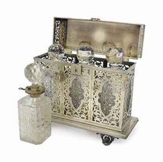 A LATE VICTORIAN SILVER TANTALUS WITH THREE CUT GLASS DECANTERS AND STOPPERS, AND AN ENGLISH SILVER MOUNTED CUT GLASS DECANTER AND STOPPER,  THE TANTALUS MARKED SHEFFIELD, 1896, PROBABLY HARRISON BROTHERS & HOWSON