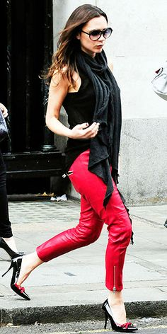 Victoria Beckham in a black top and zipped leather pants, adding patent bowed heels to complete the look.