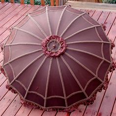A lovely 16-boned parasol with a silver toned handle, embellished with brown lace and trim.