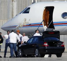 He's off: The Hollywood actor is shepherded from the steps of his private jet to a waiting...