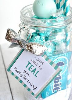 close up of open clear jar, filled with sweets and gum in teal wrappers, birthday card attached to jar with glittering silver bow