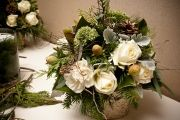 Winter wedding centerpiece with pine cones, roses, and evergreens.