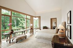 Vintage Michael Taylor lounges, in Perennials fabric, and Great Outdoors ottomans stand on a terrace off the guest suite, which occupies a separate wing. The wood doors and windows are by Architectural Millwork; the stonework is by Pat Scott Masonry.