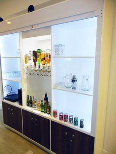 Bar cabinet. Walnut doors, steel roller shutter door, main unit spray painted high gloss white, white LED lighting.