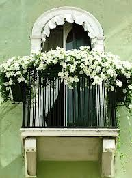 Wrought-iron faux balcony. Love flower display up top.