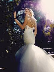 """The """"Oriana"""" gown from Lauren Elaine Bridal.   Couture Bridal by Celebrity Designer Lauren Elaine.   Life is a story. Make yours a fairytale in the dramatic backless alencon lace and tulle mermaid """"Oriana"""" wedding gown from Lauren Elaine Bridal. Featuring exquisite nude illusion open back draped in double-stranded pearls, cathedral train, lace ruffle straps, and pearl and floral lace detailing throughout. Enchantingly made in Los Angeles, CA. #laurenelainebridal"""
