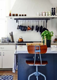This modern kitchen blends organization and style so beautifully! Recreate this sophisticated design for yourself by utilizing over-the-range storage and a dark blue pop of color.