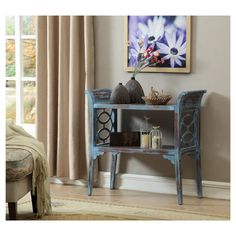 This console table is full of charm and distressed character with it's Villa Blue Rub through finish. The sides gently curve outward creating handle like sides. Open circles adorn the sides and gingerbread like corner blocks round out the area under the shelf. Whether you prefer farmhouse, cottage or a coastal look this is sure to work for your home.