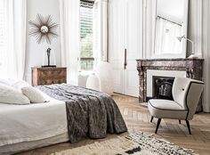 The bed in the master bedroom is dressed with beautifully textured linen from…