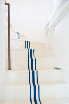 Three blue stripes in middle of painted white stairs in seaside cottage, copper pipe as handrail | Remodelista