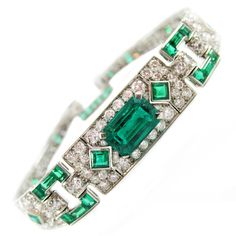 Cartier Art Deco Emerald Diamond Platinum Bracelet. Cartier Art Deco platinum diamond emerald bracelet, center emerald weighing approx. 2.4 cts, further set with 40 square and rectangle shaped emeralds, surrounded by 168 Old European cut diamonds weighing approx. 5.5 cts, signed Cartier and numbers, in original Cartier Box, c 1927