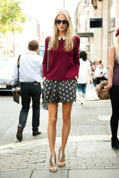 Poppy Delevingne in a wine sweater, white collared top, dark patterned shorts, and metallic strappy heels
