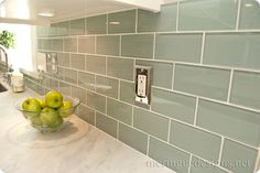 White marble counter with green subway tiles