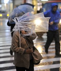 A pedestrian's umbrella is destroyed right in her hands as rains and high winds blow though Tokyo on April 3, 2012.