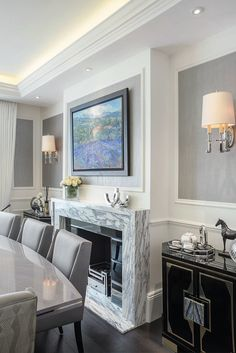 Dining room in shades of gray with defused cove lighting, wainscoting and a marble fireplace