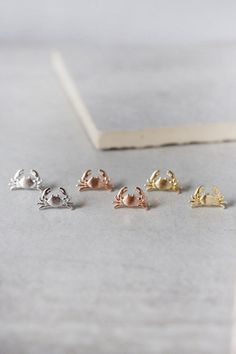 Cute and dainty Maryland Crab stud earrings in gold, silver, and rose gold.