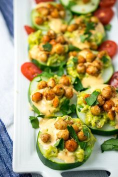 Guacamole Recipe Discover Spicy Chickpea Avocado Cucumber Bites Cucumber appetizers lined up on a white plate with a blue and white napkin beneath it. Browned chickpeas and avocado top the cucumbers with tomatoes in the background. Cucumber Appetizers, Cucumber Bites, Cucumber Recipes, Vegan Appetizers, Vegan Snacks, Appetizer Recipes, Mini Appetizers, Vegan Food, Super Healthy Recipes