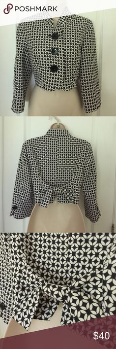 """WHBM Black/white Geo short jacket sz 6 Black & white short jacket from WHITE HOUSE BLACK MARKET   Size 6  Bust (underarm to underarm): 36""""  Length (top of shoulder to hem): 15.5 """"  Sleeve length (shoulder to cuff): 18""""  Three large black buttons on front and one on cuffs. Fully lined. Bow detail at back. 3/4 length sleeves.  Shell: 74% polyester, 26% rayon. Lining: 100% polyester.   In excellent gently used condition. No stains, tears or holes.  From a smoke free home. White House Black…"""
