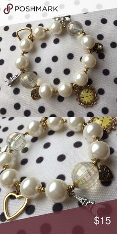 Betsey Johnson Pearl Paris Charm Bracelet Stretch elastic statement bracelet from Betsey Johnson. Bracelet includes pearls, gold beads and Paris-inspired charms, including: Eiffel Tower, open heart, two birds on a branch, gold flower with pearl detail, a clock with pink stones and a gold bow detail, and a small BJ branded heart. Betsey Johnson Jewelry Bracelets