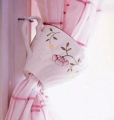 Teacup Tiebacks for Kitchen Curtains An interesting tieback adds a fun accent to kitchen curtains. To copy this look, take cups to a glass store to have 1½-inch holes drilled into the bottoms. Thread a curtain panel through a teacup. Screw a cup hook into the window frame or wall stud and hang the cup by its handle. by lorene