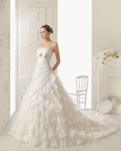 流れるように長いトレーンでシルエットも美しいウェディングドレス。生地使いが独創的でとても綺麗。
