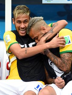 JULY 12: An injured Neymar and Dani Alves of Brazil share a joke on the bench prior to the 2014 FIFA World Cup Brazil Third Place Playoff match between Brazil and the Netherlands at Estadio Nacional on July 12, 2014 in Brasilia, Brazil.