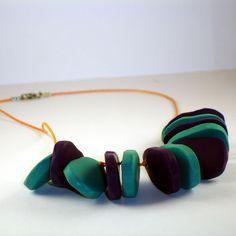 Collar de arcilla polimérica con piezas ovaladas de forma irregular en colores turquesa y lila montadas sobre un cordón de algodón en color naranja de 0,5mm. El cierre es de bisutería en color Plata envejecida.