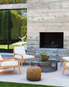 Chairs around a glass-topped coffee table beside an outdoor fireplace