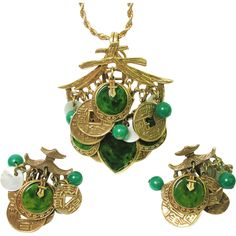 Signed ART Asian pagoda demi-parure pendant and earring set loaded with green ,  mother of pearl and gold-tone charms...