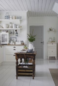 White painted wooden floors, wire baskets, open shelves, metro tiles and old wood - such a cosy atmosphere!