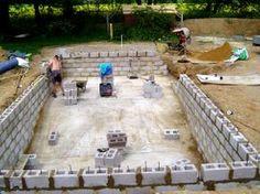 DIY with cinder blocks   Excavate site, lay reinforced concrete base and tie in blocks
