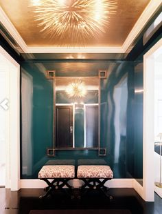 high gloss, peacock blue lacquered walls, gold leaf ceiling treatment, fabulous Jean de Merry urchin chandelier, and x-benches upholstered in an ikat fabric.