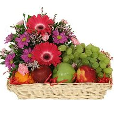 "Send this beautiful and generous combination of fresh fruits and flowers. Perfect for so many occasions and feelings or ""just because"". Two red gerberas, six pink carnations, purple daisies, gypsophila, apples, peaches and grapes. Please note that fruits are seasonal and may not be available year round."