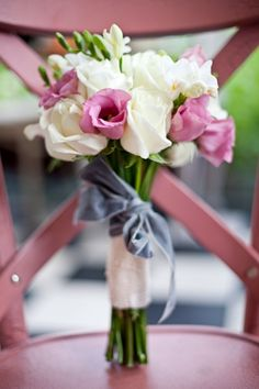 Romantic bouquet of fresia, white and pink roses all tied up with a soft lavender velvet ribbon.