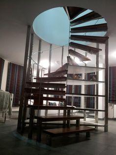 2007 Escalera de Caracol para Fran. Diseño de Ernesto Oñate. La escalera comunica dos salones en la vivienda. La estructura es de acero. Los peldaños se sujetan en la parte exterior quedando sin sujeción en el centro. Los peldaños son de madera de Elondo. En la parte posterior de la escalera se encierra una estantería con cinco estantes semicirculares lacados en blanco, para ser usados en la parte del salón inferior.