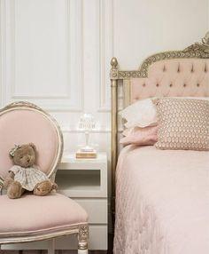 Quarto rosa e branco com cabeceira clássica e boiserie. Criado-mudo de linhas retas