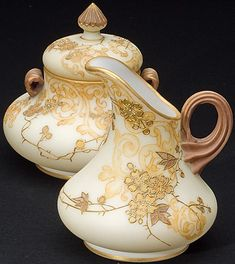 An art glass covered sugar and creamer set, Mt. Washington Glass Company, New Bedoford, Massachusetts, circa 1888 to 1895. Crown Milano with mult-color and yellow floral decoration, diminutive bulbous forms with applied reeded handles