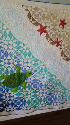 Beach quilt made to commemorate a beach wedding. Made with batiks and off white Bella solid in the storm at sea pattern with appliqué starfish and sea turtle.