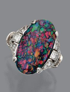 BLACK OPAL AND DIAMOND RING, CIRCA 1920 The oval-shaped black opal measuring approximately 20.5 by 11.2 by 4.9 mm., the sides accented with buckle motifs set with single-cut and baguette diamonds, mounted in platinum.